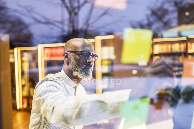 Бизнесмен, пишущий ручкой на клейкой ноте, клеящейся на оконное стекло — стоковое фото