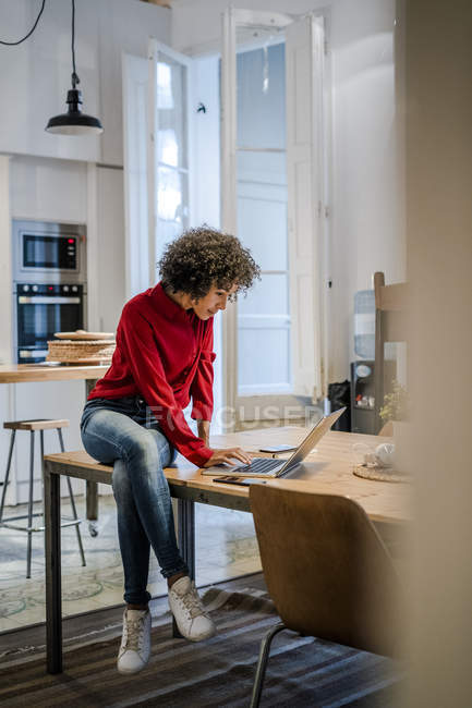 Jeune femme assise sur la table en utilisant un ordinateur portable — Photo de stock
