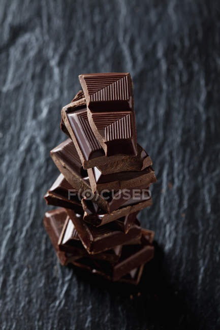 Pile de morceaux de chocolat sur ardoise noire — Photo de stock