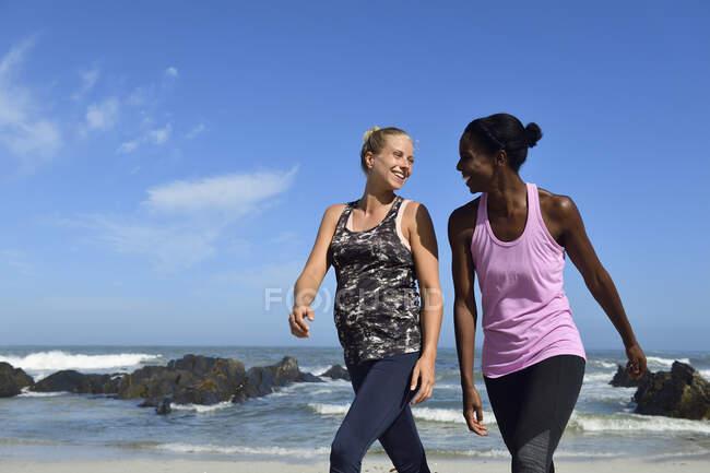 Две счастливые женщины, идущие по пляжу — стоковое фото