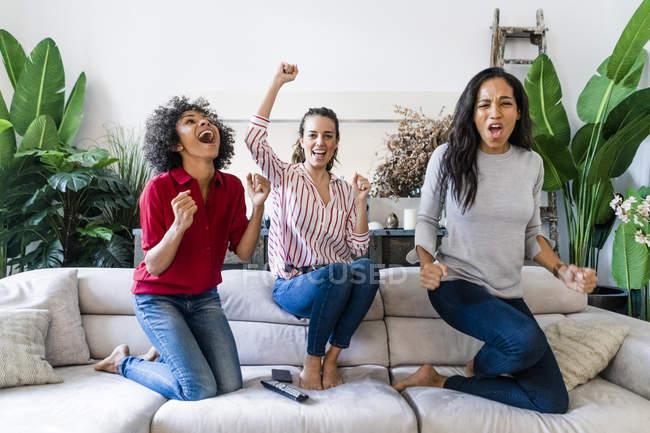 Trois femmes excitées sur le canapé à la maison regardant la télévision et acclamant — Photo de stock