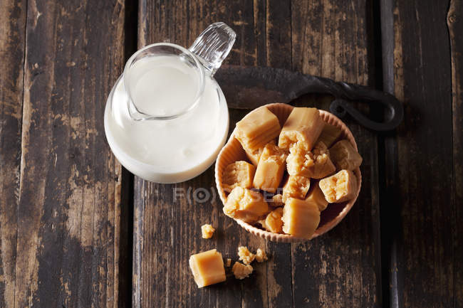 Fresh cream toffees and a carafe of cream — Foto stock