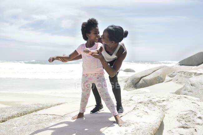 Мать и дочь делают гимнастическое упражнение на пляже — стоковое фото