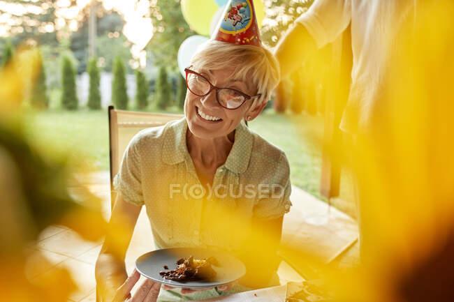 Улыбающаяся зрелая женщина держит тарелку с тортом на дне рождения — стоковое фото