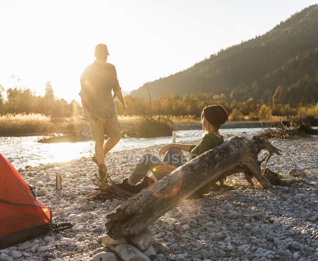 Pareja madura acampando en la orilla del río, recogiendo madera para un fuego de campamento - foto de stock