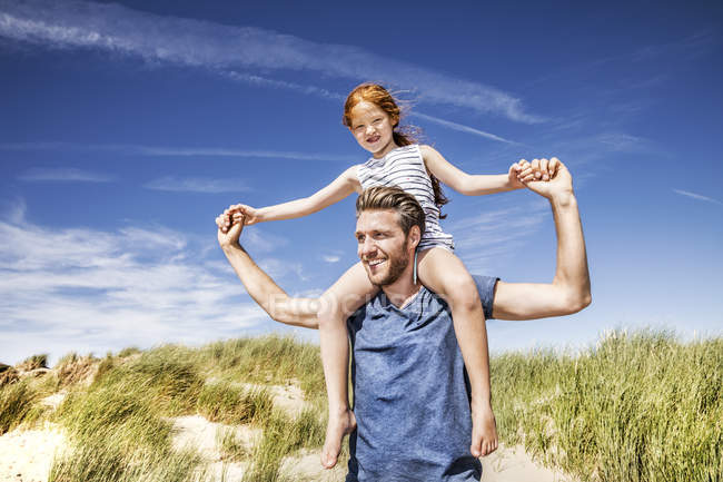 Netherlands, Zandvoort, father carrying daughter on shoulders in beach dunes — Stock Photo