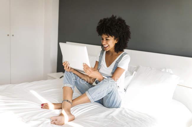 Bonne femme assise sur le lit, regardant la tablette — Photo de stock