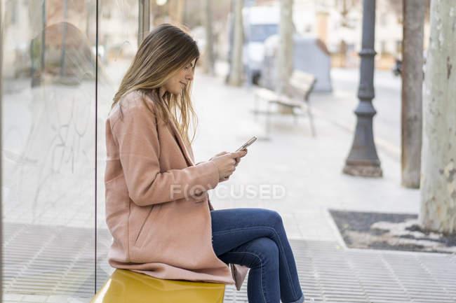 Молодая женщина с мобильным телефоном ждет на автобусной остановке — стоковое фото