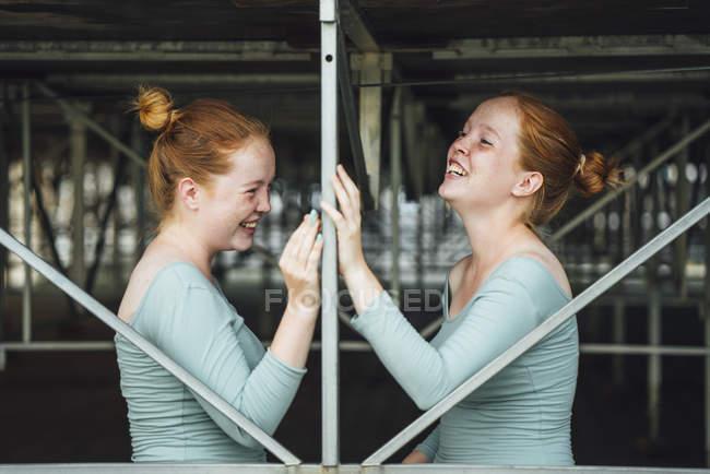 Smiling Redheaded twins under bridge — стоковое фото