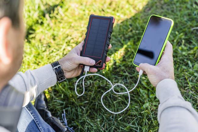 Бізнесмен заряджає свій смартфон банком сонячної енергії. — стокове фото