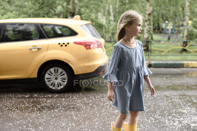 Girl wearing blue dress and vrossing road, yellow car in the background — Photo de stock