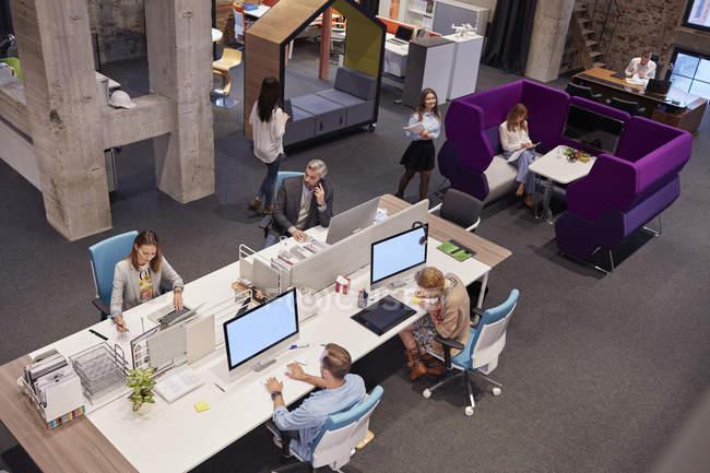 Personas que trabajan en una oficina moderna y grande - foto de stock