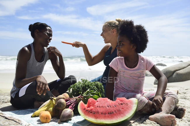 Мать с дочерью и другом на пикнике на пляже — стоковое фото