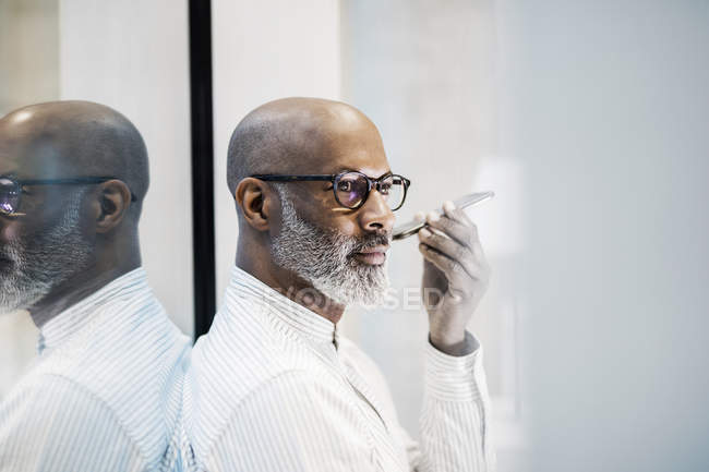 Portrait of bald mature businessman with grey beard using smartphone — Stock Photo