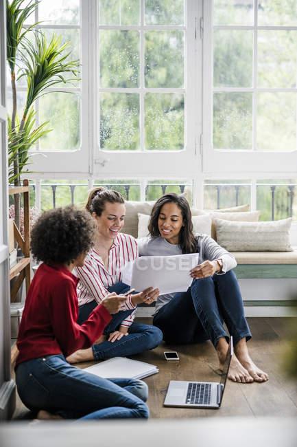 Três mulheres com laptop e documentos sentados no chão em casa — Fotografia de Stock
