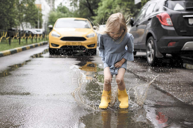 Girl wearing blue dress and rubber boots, jumping in pond on street, yellow car in the background — Photo de stock