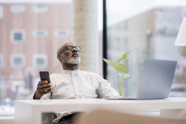 Mature businessman listening music with smartphone and earphones relaxing — Stock Photo
