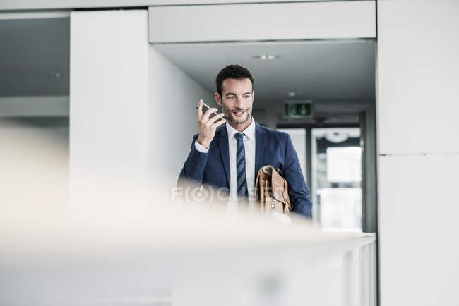 Бизнесмен с портфелем прогуливается по офисному зданию, используя смартфон — стоковое фото