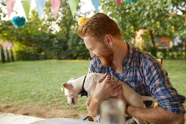 Happy man with dog on a garden party — Stock Photo