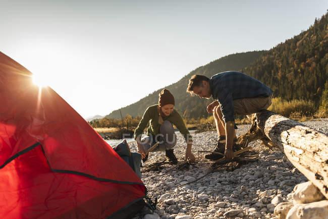 Coppia matura campeggio a riva del fiume con legna per un fuoco da campo — Foto stock