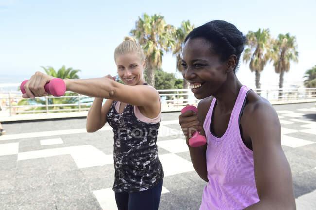 Дві щасливі жінки роблять фізичні вправи з ідіотами на відкритому повітрі. — стокове фото