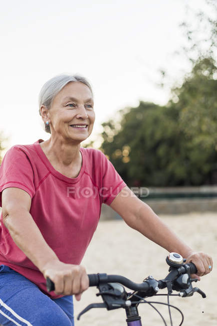 Portrait of smiling senior woman riding bicycle — Stock Photo