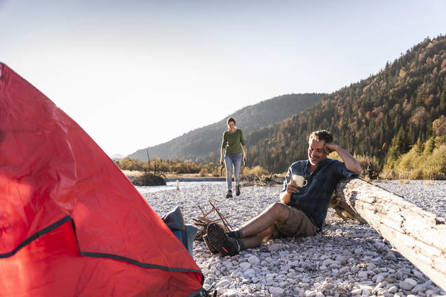 Mature couple camping at riverside in the evening light — Stock Photo