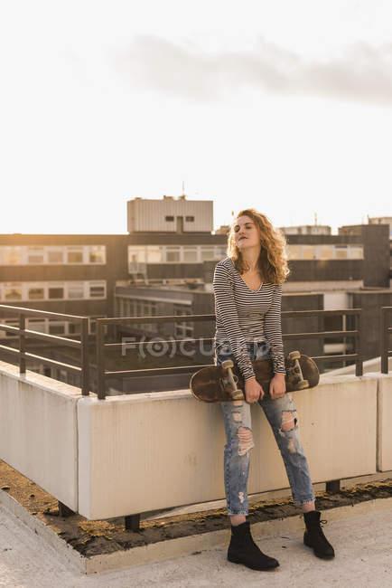 Giovane donna con skateboard godendo del tramonto sulla terrazza sul tetto — Foto stock