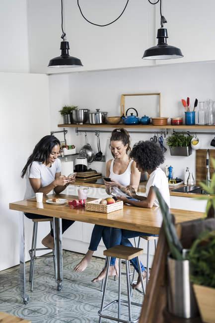 Trois femmes heureuses assis à la table de la cuisine à la maison en utilisant des téléphones cellulaires — Photo de stock