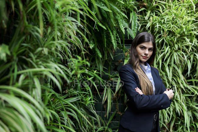 Porträt einer selbstbewussten jungen Geschäftsfrau umgeben von Pflanzen — Stockfoto