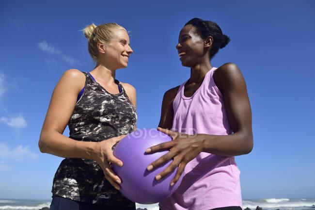 Две счастливые женщины, держащие фитнес-мяч под голубым небом — стоковое фото