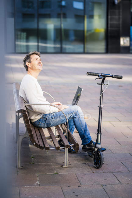 Casual businessman with kick scooter, sitting on a bench, working relaxed in the city — Stock Photo