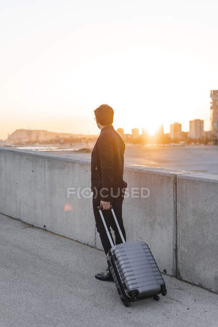 Spain, Barcelona, back view of young businessman with rolling suitcase watching sunset — Stock Photo