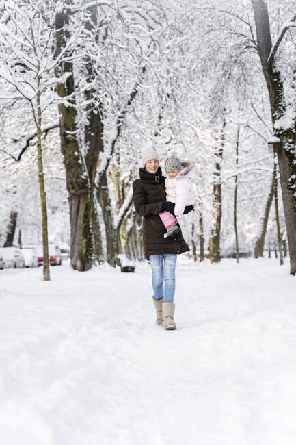Happy mother walking with daughter in winter landscape — Stock Photo