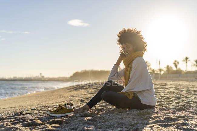 Женщина сидит на пляже на закате — стоковое фото