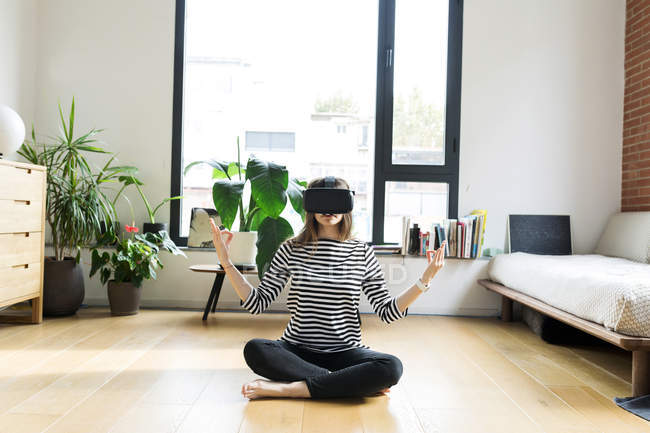 Молодая женщина дома в VR очках и занимается йогой — стоковое фото
