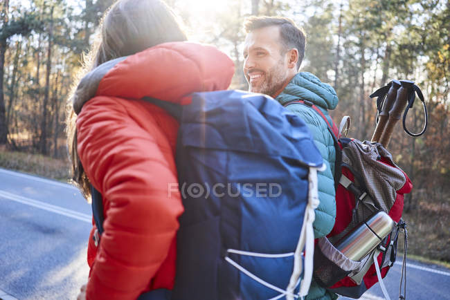 Happy couple walking along road in the woods during backpacking trip — Stock Photo