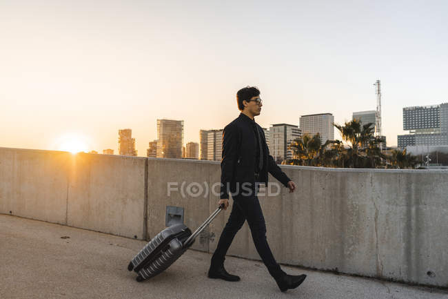 Spain, Barcelona, young businessman with rolling suitcase at sunset — стокове фото