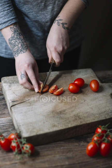 Young woman cutting tomatoes on chopping board — Stock Photo