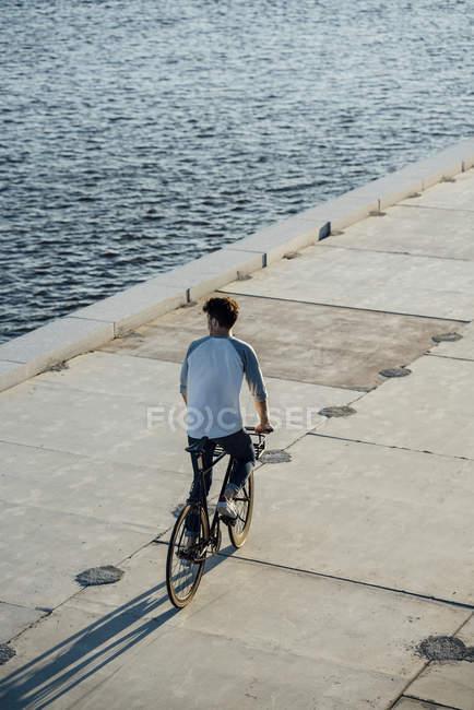 Jeune homme conduisant le vélo sur la promenade de front de mer au bord de la rivière — Photo de stock