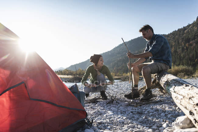 Pareja madura acampando en la orilla del río, con madera para una fogata - foto de stock
