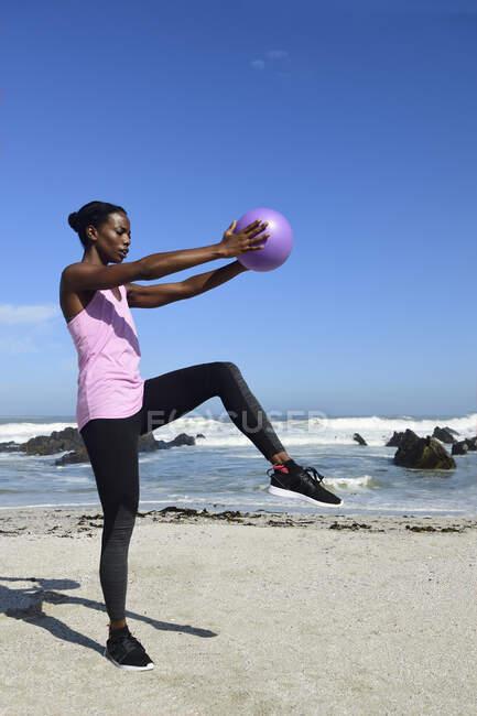 Женщина занимается фитнесом с мячом на пляже — стоковое фото