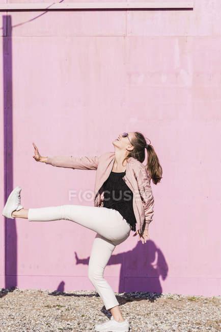 Счастливая молодая женщина движется перед розовой стеной — стоковое фото