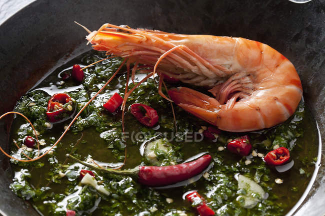 Prawn with herbs, chili and garlic in iron pan — Stock Photo