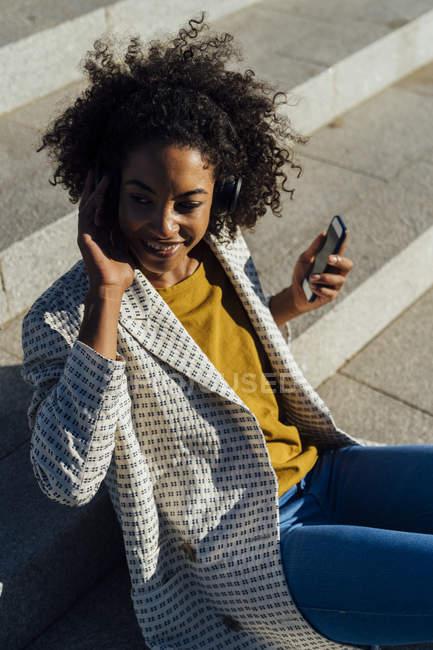 Женщина сидит на лестнице в городе, используя смартфон, слушая музыку в наушниках — стоковое фото