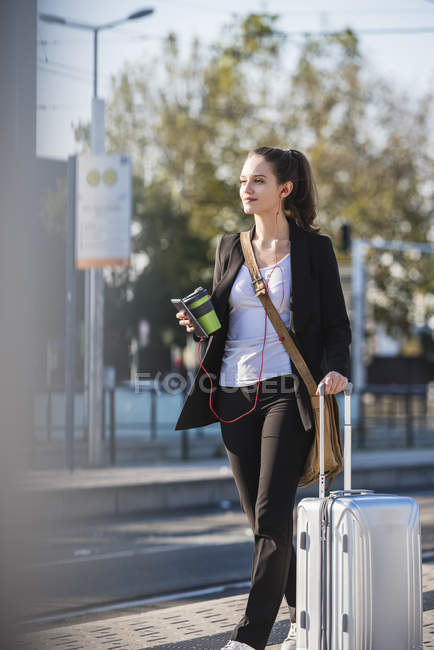 Young woman with luggage at tram station on the move — Stock Photo