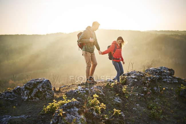 Coppia in escursione in montagna camminando sulle rocce — Foto stock