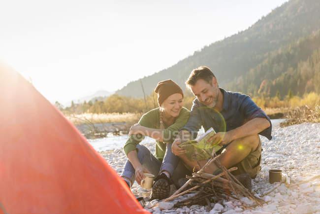 Campant de couples mûrs au bord de la rivière, regardant sur la carte — Photo de stock