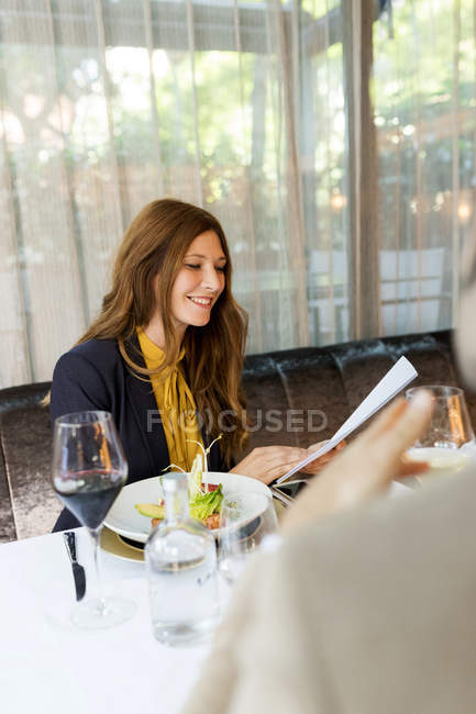 Smiling woman with man in a restaurant holding documents — Stock Photo