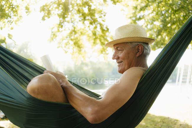 Älterer Mann mit Strohhut entspannt in Hängematte am Seeufer beim Lesen von Buch — Stockfoto